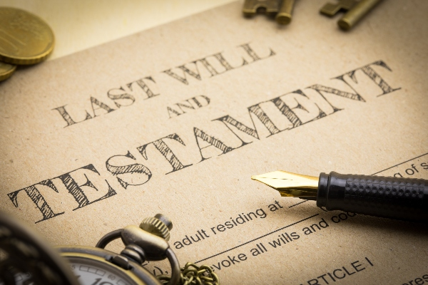 A will and trust document is front and center with legal notes beside it.